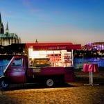 Das rote Espressomobil vor Hohenzollernbrücke und Dom in Köln bei Nacht