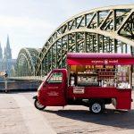 Das rote Espressomobil vor Hohenzollernbrücke und Dom in Köln