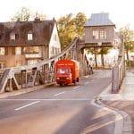 Das rote Espressomobil fährt auf einer Brücke aus dem Kölner Rheinauhafen